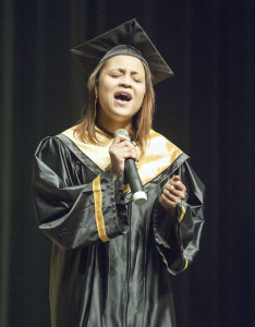 Jashuna Richard, a 2013 Ombudsman graduate, sings the national anthem during Wednesday's commencement. Photo by Brandon Powers