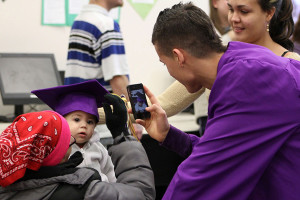 Luis Ballester Marti takes a photograph of his niece wearing his graduation cap after the ceremony at the Ombudsman Center. (Caitlin Dumas/Independent)