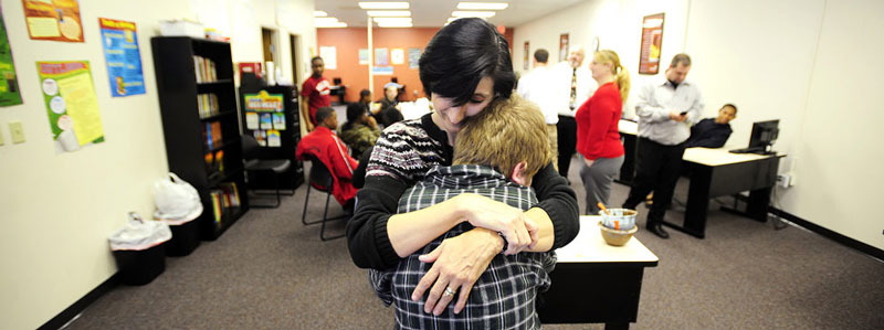 Donna Wagman embraces her son, Caleb, at the school.