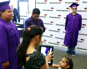 Jesse Adams poses for a pictures with his shades on after graduating Tuesday at the Grand Island Ombudsman Center. Thirteen students were in the graduating class of 2013, many overcoming unique challenges to earn their diploma. (Independent/Matt Dixon)