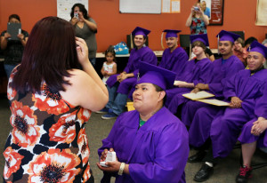 After receiving his diploma, Mainor Tercero purposes to Stephanie Morales during graduation Tuesday at the Grand Island Ombudsman Center. She said yes. (Independent/Matt Dixon)