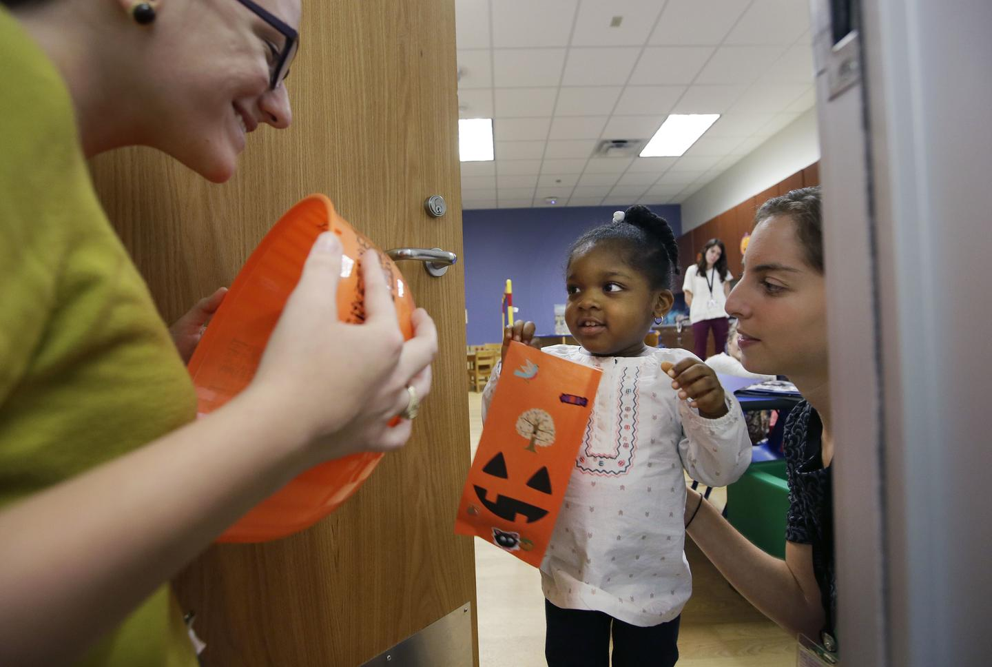 Picture of young female student at the door to a classroom holding a jack 'o lantern bag for Halloween candy. One teacher is beside her inside the classroom. Another teacher is at the door with a Halloween candy bowl.