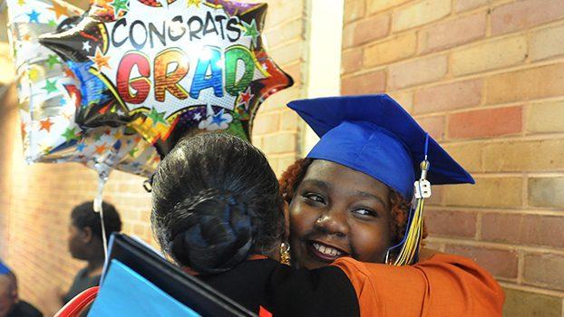 "Natchez-Adams Ombudsman School graduate hugs a family member while holding a ballon that reads ""CONGRATS GRAD"""