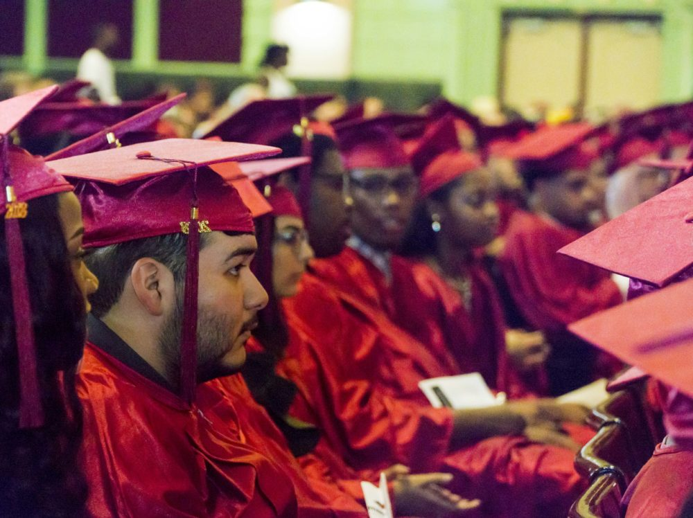 2018 Ombudsman Chicago graduates sitting in a group in red caps and gowns