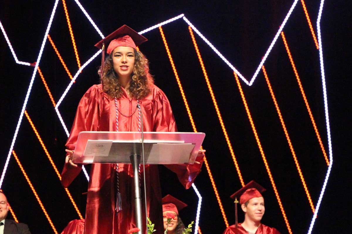 A graduate in a red robe and cap stands on stage behind a podium delivering a commencement address as other graduates, seated to the rear, look on
