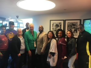 Toni Preckwinkle, and all Ombudsman team members and community partners present, pose for a group picture. Everyone is standing smiling against one of the walls of the box suite, in front of some historic black & white framed football photographs.