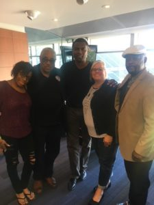 State Rep La Shawn Ford stands smiling in the middle of the photo, between retired State Rep Paul Williams, and smiling Ombudsman team members. The group is posed in front of a sunny window.