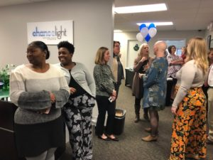 ChanceLight employees are gathered together in the lobby of ChanceLight's Nashville office, smiling and enjoying socializing at the Servant Heart Award reception.